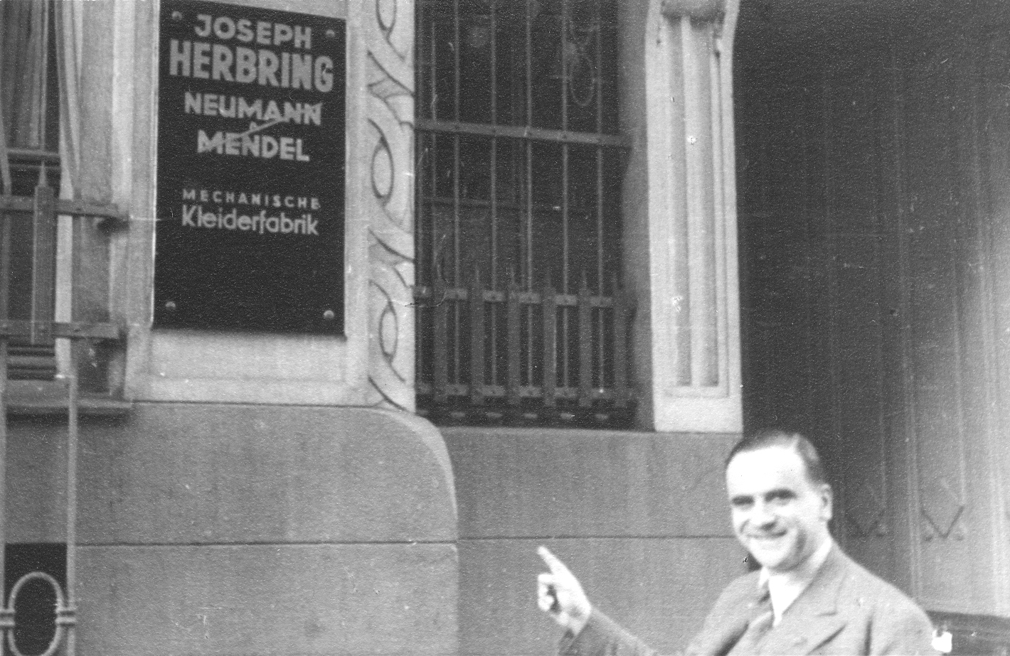 Ludwig Neumann pointing to the sign at the entrance of the Josep Herring textil factory, former Neumann & Mendel's. © Wiener Library Photo Collection